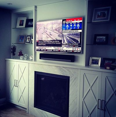 "A #Samsung #UN55JS8500 55"" #4K TV and #Sonos #Playbar mounted over a fireplace. A Sonos #Sub sits behind the sofa."