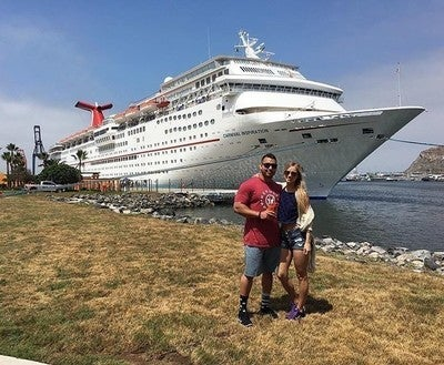 A Posing For Photo In Front Of The Carnival Inspiration Ensenada