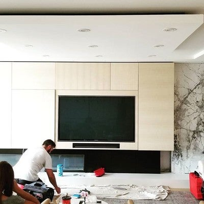 "Jordan putting the finishing touches on a #RecessedTV and #Sonos #playbar.  An #articulating mount holds this 65"" #Panasonic #Plasma 15"" off the wall and floats flush with the millwork.  Millwork and #condo design by #PaulaHimmelDesign"